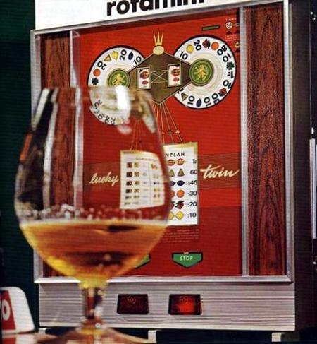 Ein fast leeres Bierglas vor dem Geldspielgerät