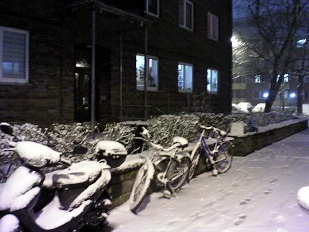 Fahrräder und Motorroller im Schnee