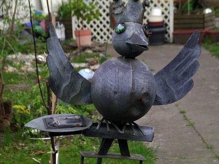 Ein ausgesprochen hässliches Dekorationsobjekt in einem Garten, ein rabenähnliches Gebilde aus Blech