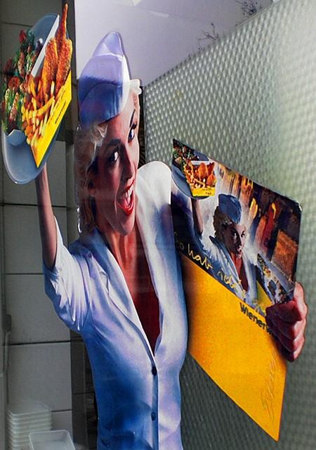 Werbung an einer Fensterscheibe einer Wienerwald-Filiale. Hinter der perspektivisch verzerrten, auf die Scheibe geklebten, aufreizend in die Kamera ekstatisierenden Frau mit dem Müllfraß in der Hand sind die Kacheln und einige Einweg-Plastikteller sichtbar.