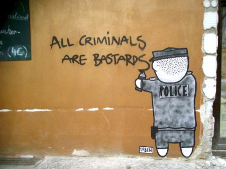A policeman sprays: All criminals are bastards.