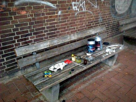 Dekorativ von Kindern auf einer Bank ausgebreiteter Müll vom Spielplatz