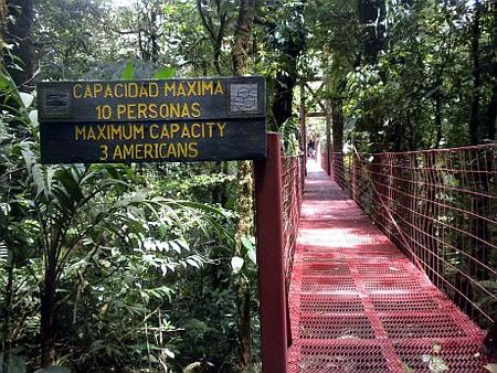 Schild an einer provisorisch aussehenden Brücke in der Wildnis: Capacidad maxima 10 personas. Maximum capacity 3 americans.
