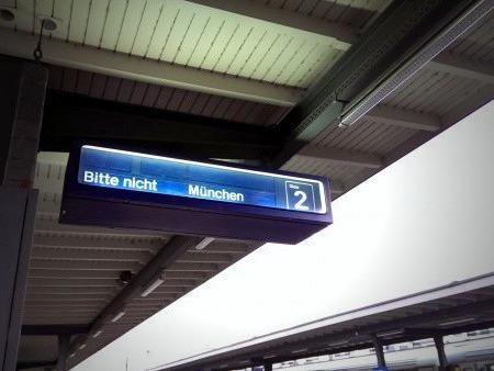 Anzeige an einem Bahngleis, offenbar mit Fehlfunktion, die 'Bitte nicht München' anzeigt