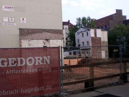 Alte Werbung eines Getränkemarktes mit Bezug auf ein inzwischen abgerissenes Haus, verschiedene Biersorten, Pfeil 'Auf dem Hof' -- davor die abgesperrte Grube einer Baustelle