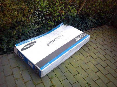 Verpackung eines Samsung-Fernsehers, die über eine Hecke geworfen wurde. Aufdruck auf der Verpackung: Smart TV