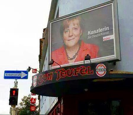Einbahnstraße. Über einer Kneipe ein CDU-Wahlplakat mit Angela Merkel, Spruch: Kanzlerin für Deutschland. Die Kneipe heißt 'Zum Teufel'.