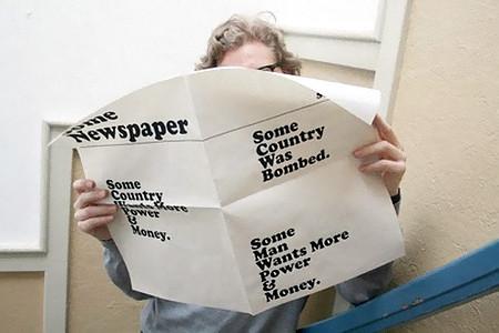 Mann liest eine Zeitung namens 'Some Newspaper'. Es sind nur drei großgedruckte Textchen erkennbar: 'Some Country Wants More Power And Money', 'Some Man Wants More Power And Money' und 'Some Country Was Bombed'.