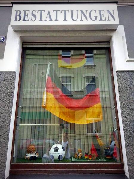 Foto vom Schaufenster eines Bestatters mit Fußball und Schlandfahnen.