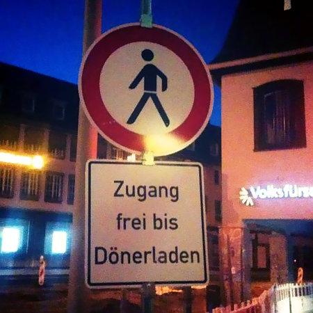Verbotsschild an einer Straße: Nicht für Fußgänger. Darunter ein Hinweisschild: Zugang frei bis Dönerladen