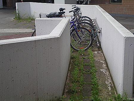 Mit Betonelementen abgegrenzter Durchgang, an dessen Ende ein gut benutzer Fahrradständer an den Beton geschraubt wurde, so dass man gar nicht durchkommen kann.
