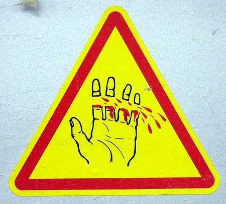Sehr explizites Warnschild mit einer Hand, von der die Finger abgetrennt wurden.