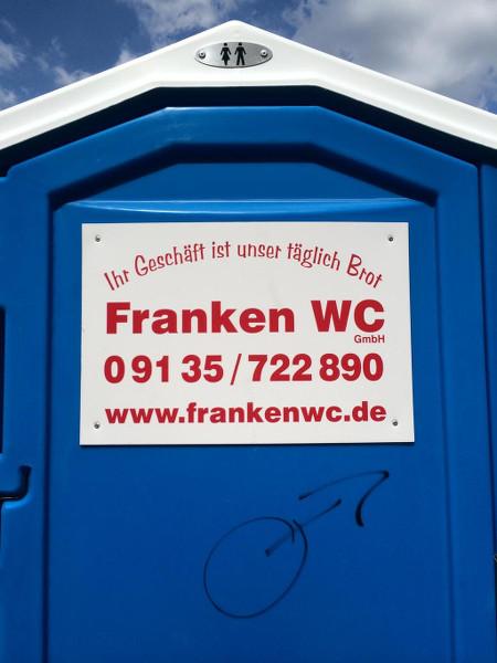 Werbung auf einem Chemie-Klo: Ihr Geschäft ist unser täglich Brot -- Franken WC GmbH -- Telefonnummer und Website