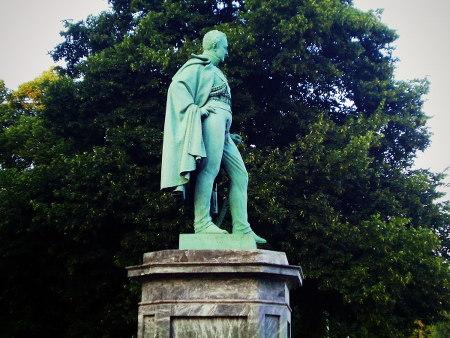Ein grün-oxidiertes Denkmal vor grünen Bäumen