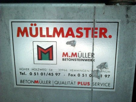 Werbeaufkleber auf einem Müllcontainer: 'Müllmaster'. Anschrift ist 'Hoher Holzweg 54