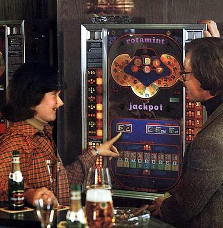 Ausschnitt aus einer Werbung für das NSM-Geldspielgerät Rotamint Jackpot aus dem Jahr 1978. Ein Mann und eine Frau stehen in einer Kneipe vor dem Geldspieler, auf dem eine Serie läuft, die Frau zeigt mit ihrem Finger auf den Sonderspielezähler, der 39 anzeigt.