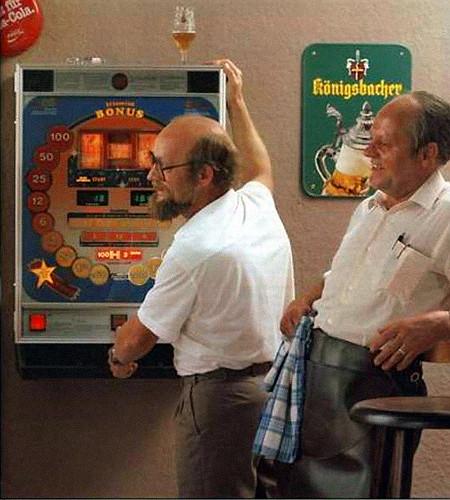 Werbung für das NSM-Geldspielgerät Triomint Bonus: In einer schlecht gestellten Kneipenszene spielt ein Mann mit nur geringem schauspielerischen Talent am Triomint Bonus, der Wirt lehnt sich lachend an den Tresen. An der Wand Werbung für Coca-Cola udn eine Biermarke 'Königsbacher'.