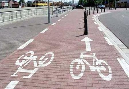 Absurde Geradeaus-Pfeil auf einem Radweg, der direkt auf einen Pfosten führen würde.