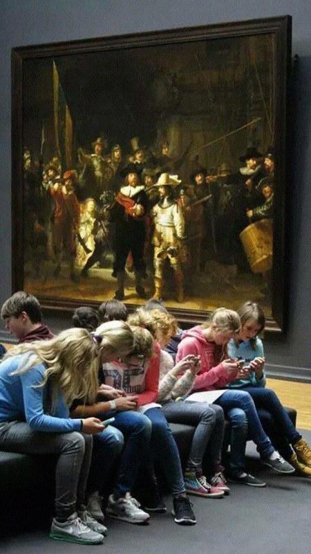 Schüler sitzen in einem Museum von einem Rembrandt-Gemälde, jeder und jede einzelne davon abgewandt und mit seinem oder ihrem Handy beschäftigt