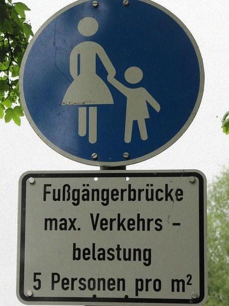 Verkehrsschild 'Fußweg' mit dem Zusatzschild 'Fußgängerbrücke max. Verkehrsbelastung 5 Personen pro m²'