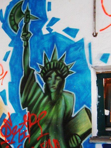 Graffito: Die Freiheitsstatue mit geschlossenen Augen, in der Hand hält sie eine Axt empor.