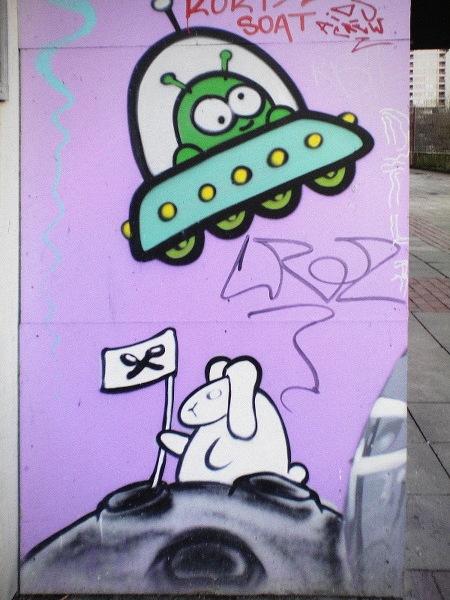 Absurdes Graffito am Ihmezentrum. Auf einen kleinen Planeten sitzt ein weißer Hase, steckt eine Flagge mit zwei gekreuzten Löffeln in den Boden. Darüber ein UFO.