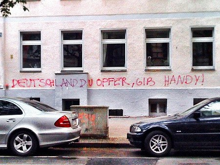 Graffito: DEUTSCHLAND DU OPFER, GIB HANDY!