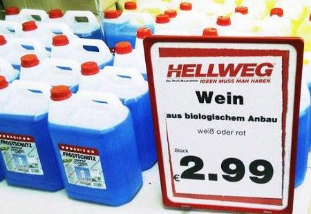 Preisschild 'Wein aus biologischem Anbau' vor Kanistern mit Frostschutzmittel
