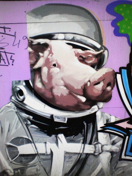 Ein ursprüngliches Graffito von einem Astronauten wurde von einem zweiten Sprayer so übersprüht, dass ein überdimensionierter Schweinekopf aus dem Helm des Astronauten hervorschaut.
