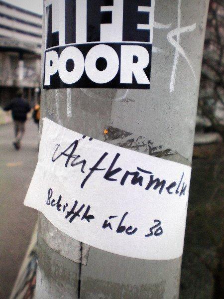 Zwei Spuckies auf einem Laternenmast. Oben: 'Life Poor', darunter: 'Aufkrümeln... Bekiffte über 30