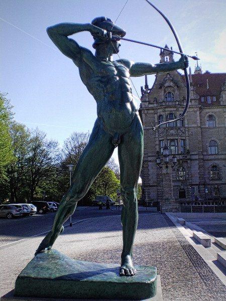 Skulptur vorm hannöverschen Rathaus: Ein nackter Bogenschütze mit gespanntem, auf den Eingang des Rathauses gerichtetem Bogen.