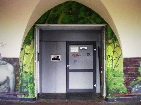 Eine Tür aus Metall, die gar nicht zu dem alten Säulengang eines Kinos nd den Graffiti drumherum passen will