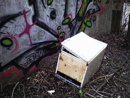 Ein wild 'entsorgter', kaputter Kühlschrank vor einer Betonwand mit Graffiti