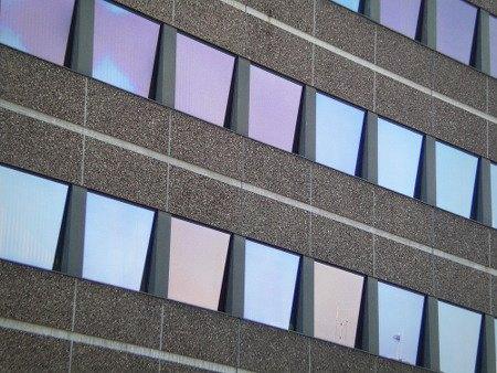 Fenster in einer hässlichen Fassade, der Himmel spiegelt sich vergebens in ihnen