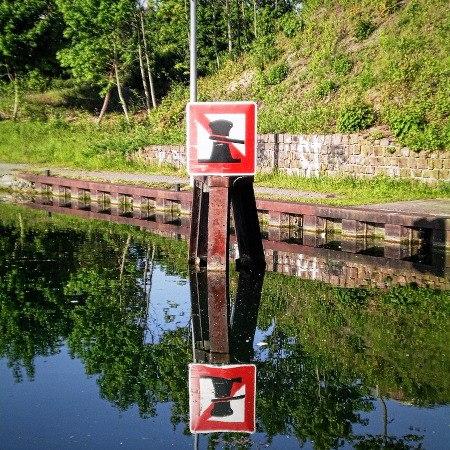Verkehrsschild und Uferbewuchs spiegeln sich an einem hellen Sonnentag in einem Kanal