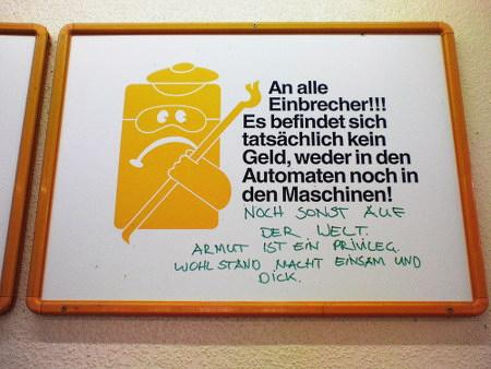 Schild in einem Waschsalon: An alle Einbrecher!!! Es befindet sich tatsächlich kein Geld, weder in den Automaten noch in den Maschinen! -- Darunter ein Graffito: Noch sonst auf der Welt. Armut ist ein Privileg. Wohlstand macht einsam und dick.