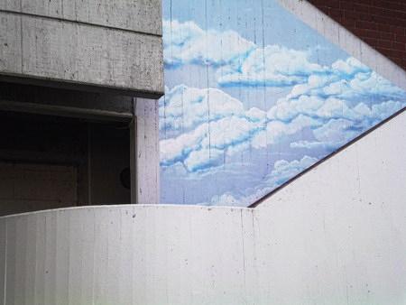 Dekorative Wandbemalung am Ihmezentrum zu Hannover-Linden: Auf den rohen Beton (die Struktur der früheren Verschalung ist gut zu erkennen, wie es typisch für den Brutalismus ist) wurde ein Himmel mit hübschen Wölkchen aufgemalt.