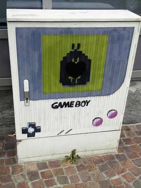 Grafitto an einem Telefonverteilerkasten, das die Bedienelemente und das Display eines Gameboy von Nintendo nachahmt
