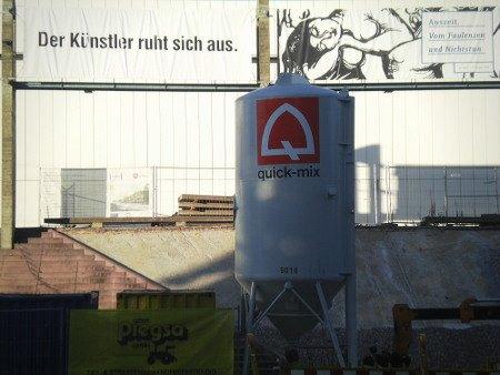 Stillleben von der gegenwärtigen Baustelle am Sprengelmuseum in Hannover. Am Museum ein Transparent 'Der Künstler ruht sich aus.', davor steht ein riesiger Betonbehälter 'quick-mix'.