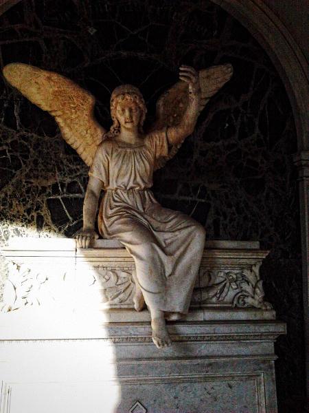 Engel auf einem Grabmal auf dem hannöverschen Friedhof Engesohde, scheinbar im Schatten sitzend und Vorübergehende zu sich winkend.