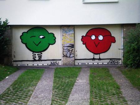 Zwei Garageneinfahrten in Hannover-Linden mit zwei dicken, grotesken Vögeln als Graffito, einer in grün und einer in rot. Der grüne Vogel zwinkert dem roten zu.