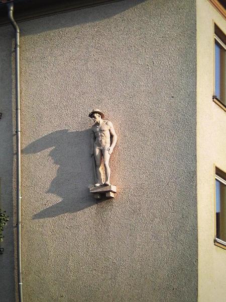 Skulptur eines Menschen an einer ansonsten kahlen Fassade, von der sommerlichen Abendsonne beleuchtet