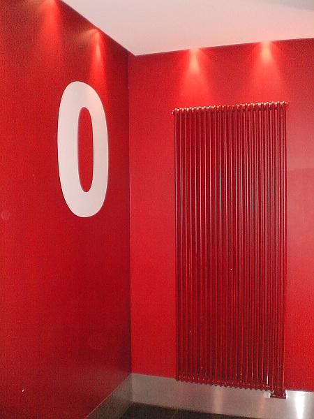 Eine rote Wand vor einem Aufzug, auf die eine große Null gemalt wurde, daneben ein riesiger, ebenfalls roter Radiator