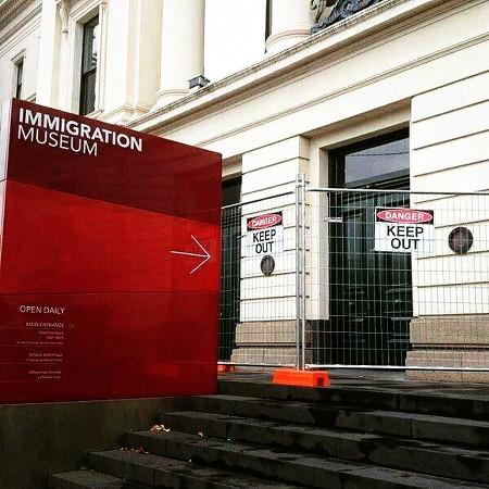 Hinweisschild: 'Immigration Museum', der Pfeil deutet auf eine Absperrung mit den Worten 'Keep out!'