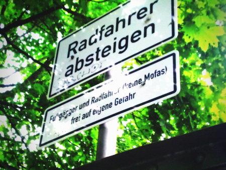 Zwei Schilder direkt übereinander. Das obere: 'Radfahrer absteigen!', das untere 'Fußgänger und Radfahrer (keine Mofas) frei auf eigene Gefahr'.