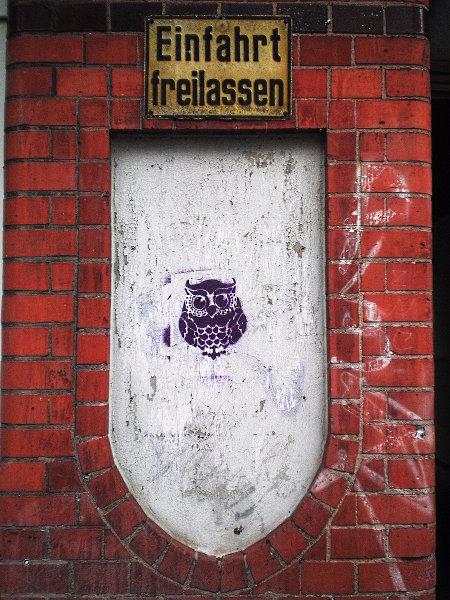 Schild 'Einfahrt freilassen', darunter ein Graffito, eine mit Schablone gesprühte Eule.