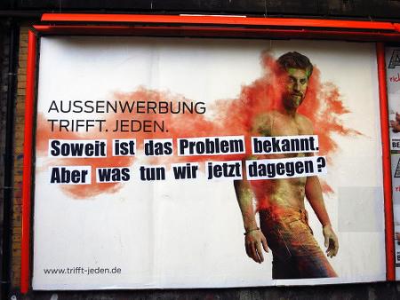 Plakat: 'Außenwerbung trifft jeden', mit aufgeklebtem Spruch: 'Soweit ist das Problem bekannt. Aber was tun wir jetzt dagegen?'.