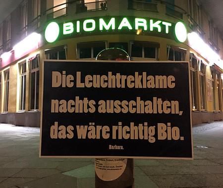 Mit Leuchtreklame erleuchteter 'Biomarkt', davor ein aufgestelltes Schild: 'Die Leuchtreklame nachts ausschalten, das wäre richtig Bio. Barbara.'