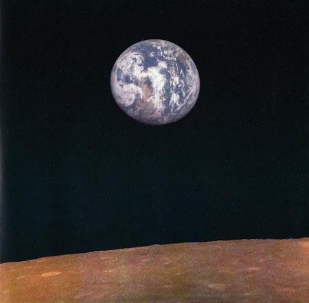 Foto der Mondoberfläche, die gerade überflogen wird, darüber die Erde