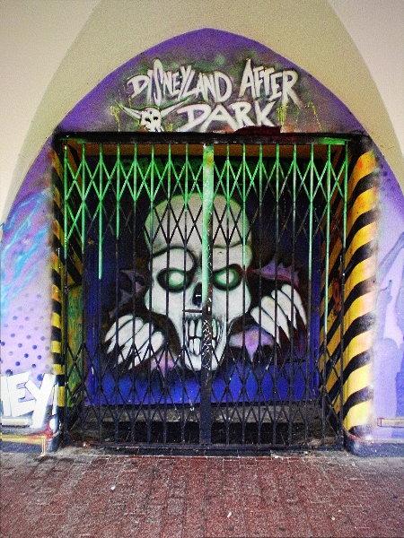 Graffito am Capitol in Hannover-Linden. In der Tür ein Totenkopf, darüber der Schriftzug 'Disneyland after dark'.